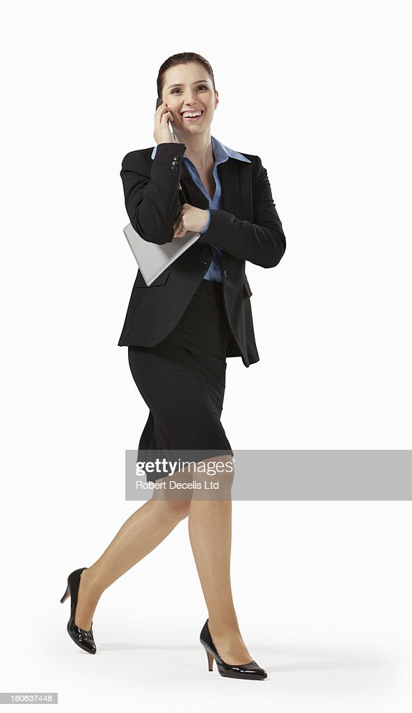 Happy business woman running whilst on smart phone : Stock Photo