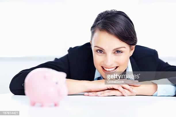 Felice donna d'affari con un Salvadanaio a porcellino al tavolo