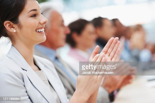 Happy business woman with colleagues applauding at a seminar