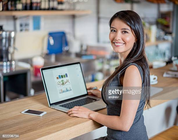 Happy business woman working at a cafe