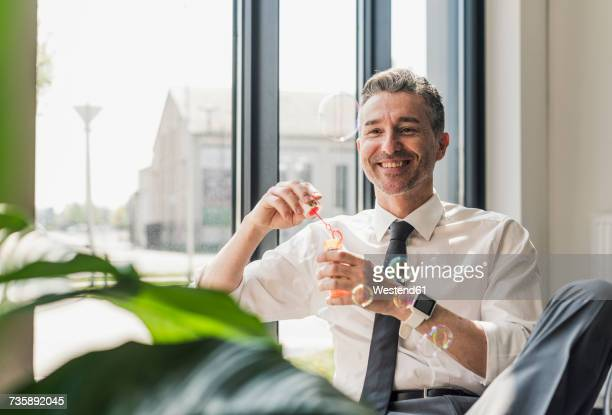 Happy businessman blowing soap bubbles in his office