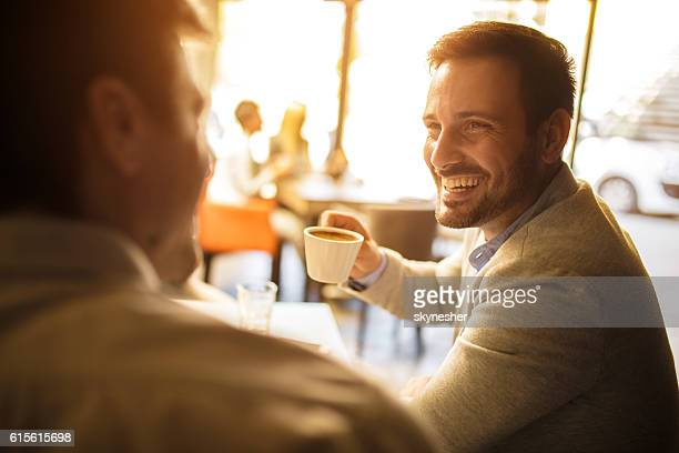 Happy businessman communicating with coworker during coffee break.