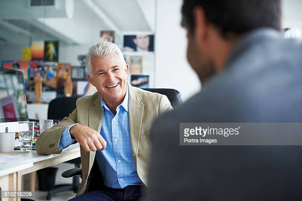 Happy businessman discussing with colleague