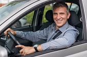 Closeup Of A Smiling Mature Businessman Parking The Car
