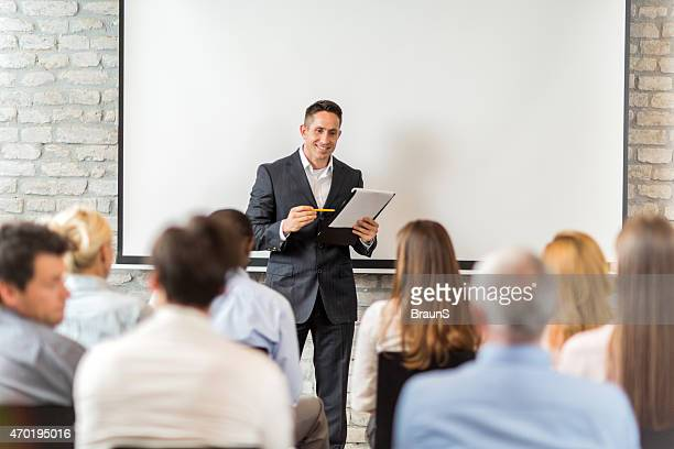 Happy businessman giving presentation to group of people.