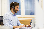 Close up of a hipster man in conference call on laptop at his desk