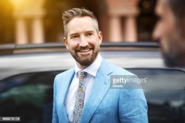 Happy businessman looking at friend by car