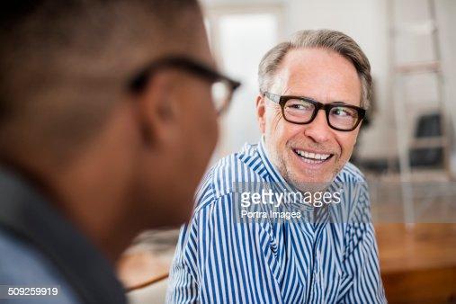 Happy businessman looking away in creative office