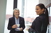 Happy businessman man and businesswoman having coffee in office