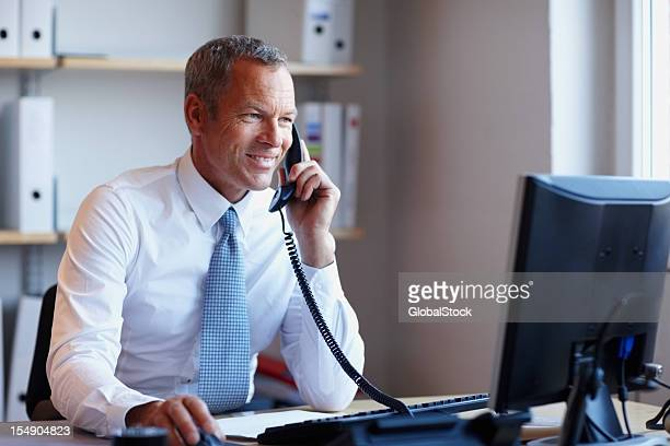 Happy businessman on phone while using computer in the office