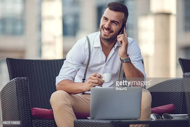 Glücklich Geschäftsmann auf Handy in ein Café.