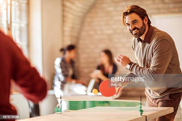 Happy businessman playing table tennis with his colleague at office.