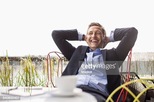 Happy businessman relaxing at outdoor cafe against clear sky
