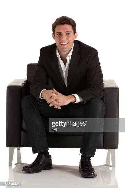 Happy businessman sitting in an armchair