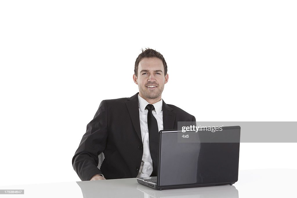 Happy businessman sitting in front of a laptop : Stock Photo