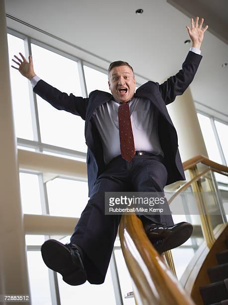 Happy businessman sliding down stair railing