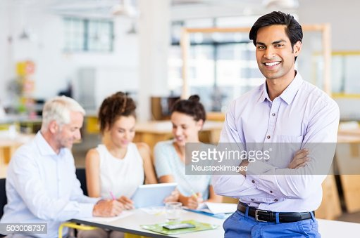 Happy Businessman Standing Arms Crossed At Office