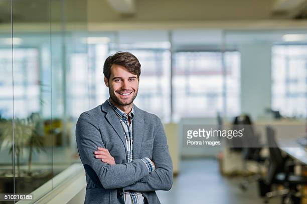Happy businessman standing arms crossed in office