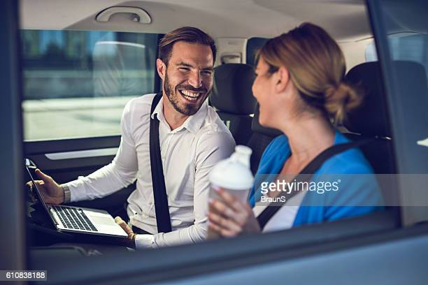 Happy businessman talking to his female colleague in the car.