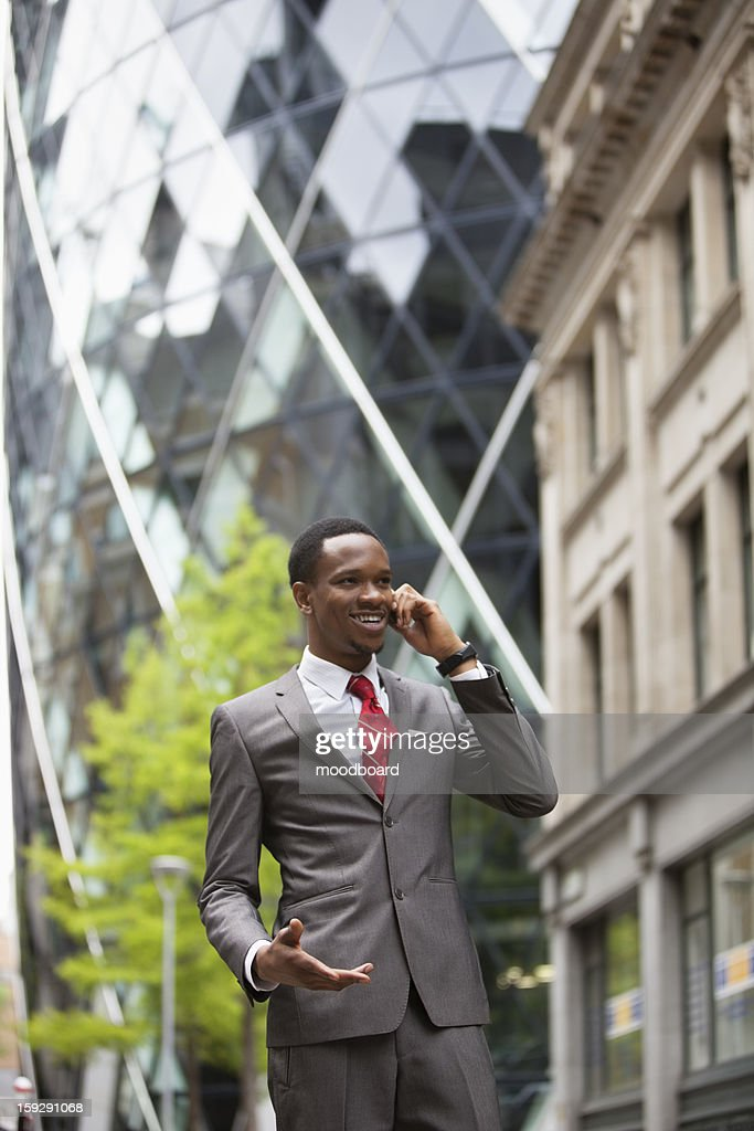 Happy businessman using cell phone outside building : Stock Photo