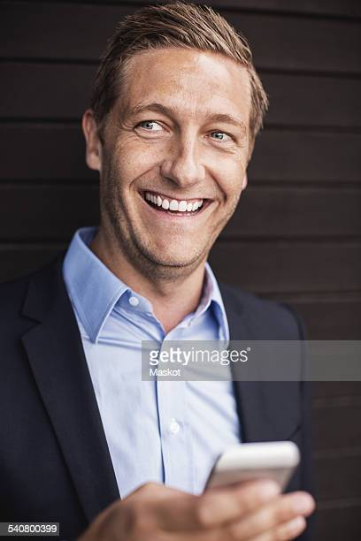 Happy businessman using smart phone
