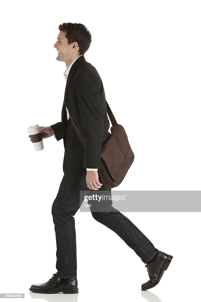Happy businessman walking with coffee