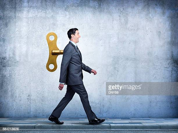 Happy Businessman Walking With Wind Up Key In His Back