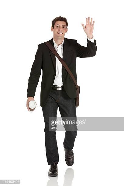 彼の手を振るハッピーなビジネスマン