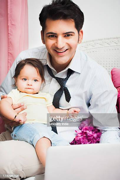 Happy businessman with his baby sitting on his lap