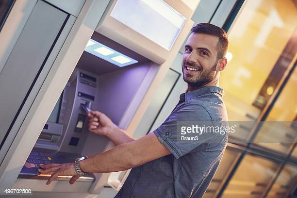 Happy businessman withdrawing money from a cash machine.