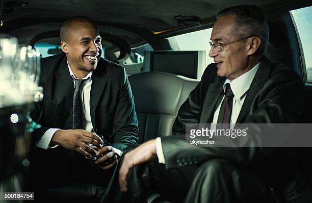 Happy businessmen driving in a limousine and talking.