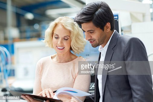 Happy businesspeople in factory with clipboard