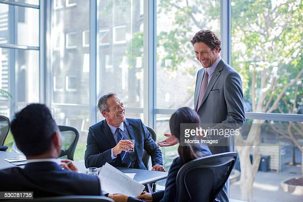 Happy businesspeople talking in board room