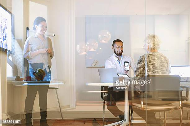Happy businesspeople using technologies in office