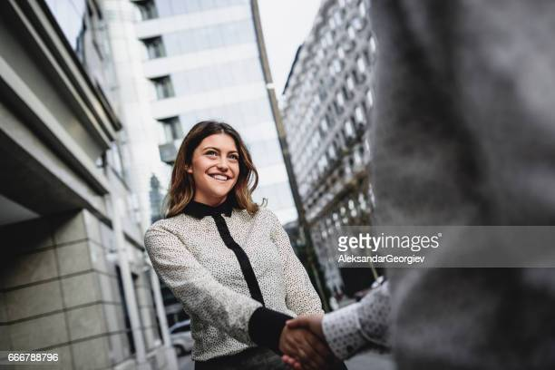 Happy Businesswoman and Businessman Handshake in Front of Office