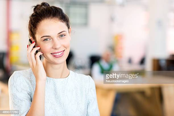 Happy Businesswoman Answering Smart Phone