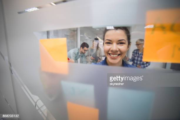 Happy businesswoman applying adhesive notes on the glass wall and looking at the camera.