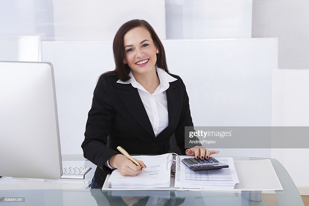 Happy Businesswoman Calculating Tax : Stockfoto