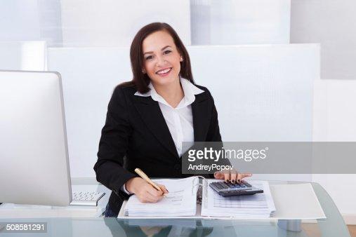 Happy Businesswoman Calculating Tax : Stockfoto