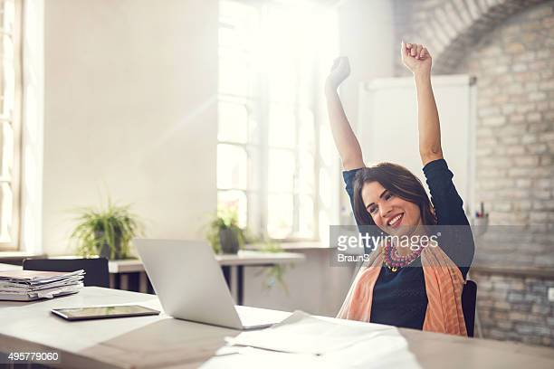 Happy businesswoman celebrating good news in the office.