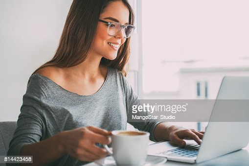 Happy businesswoman drinking coffee at laptop : Stock Photo