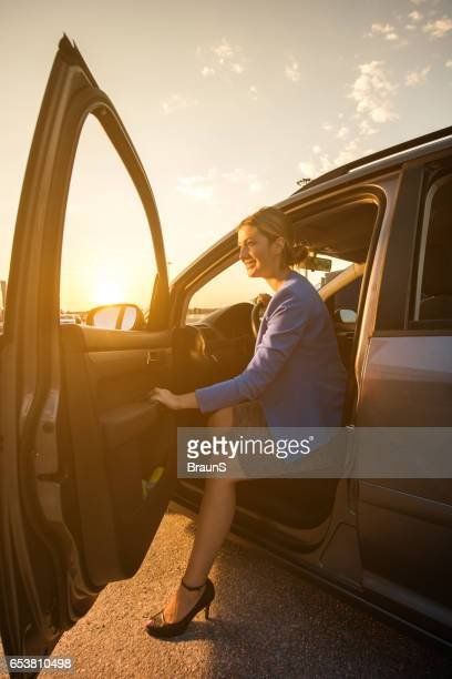 Happy businesswoman getting out of the car at sunset.
