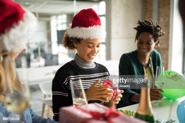 Happy businesswoman holding Christmas gift in office