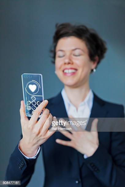 Happy Businesswoman Holding Transparent Smartphone With Heart Shape