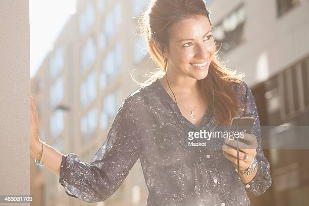 Happy businesswoman looking away while listening music through mobile phone outdoors