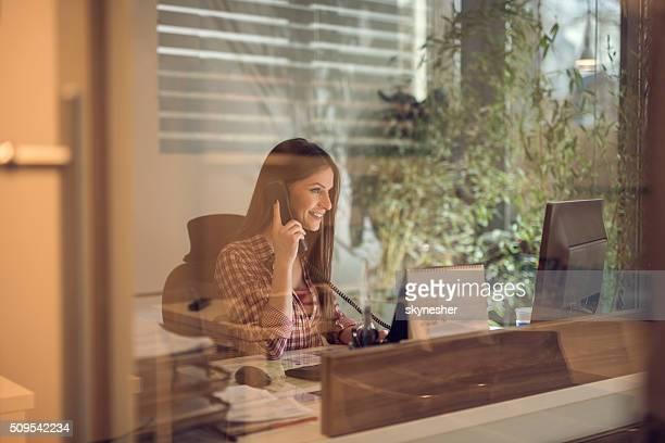 Feliz Mulher de Negócios ao telefone no escritório.