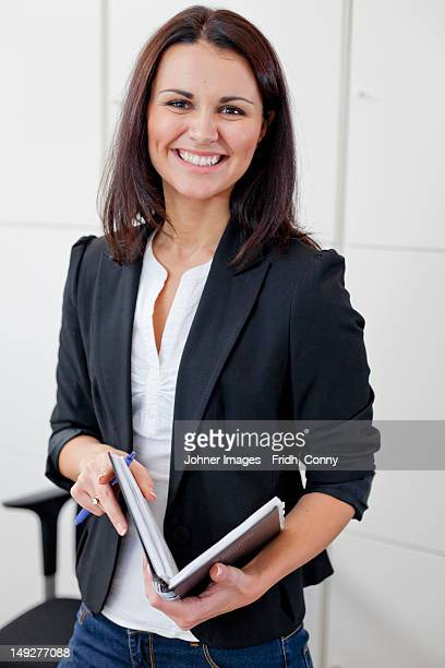 Happy businesswoman portrayed in office environment