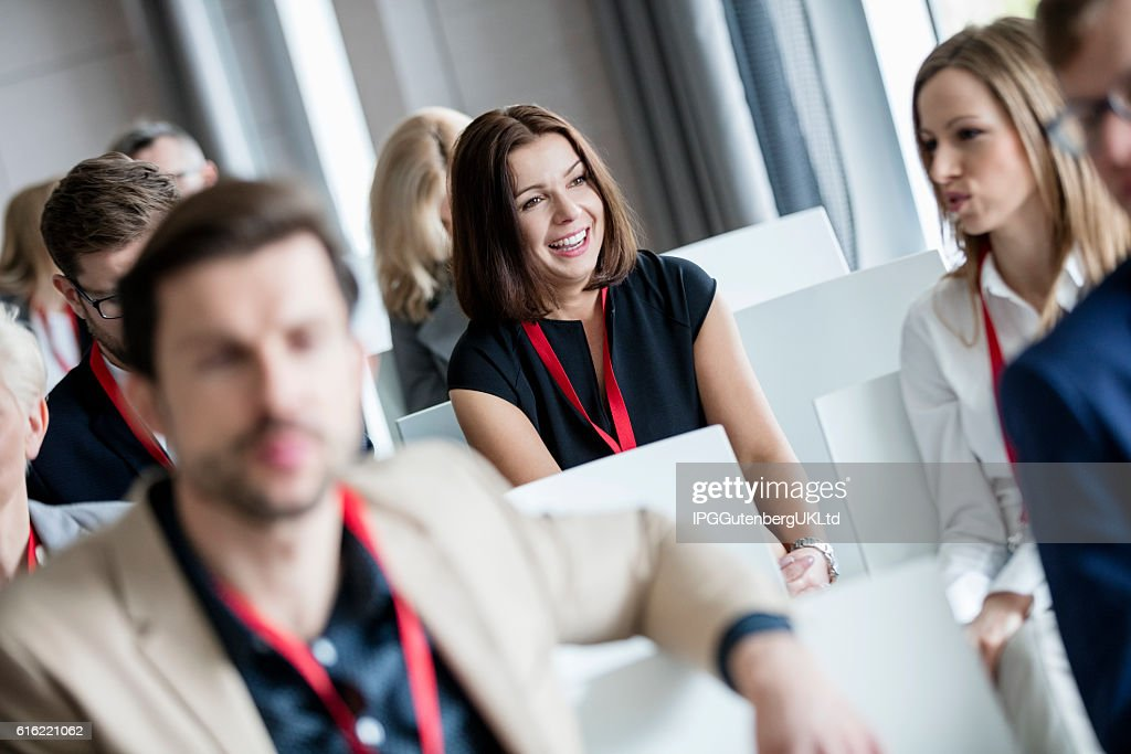 Happy businesswoman sitting with colleagues in seminar hall : Stockfoto