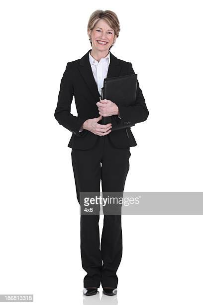 Happy businesswoman standing with files