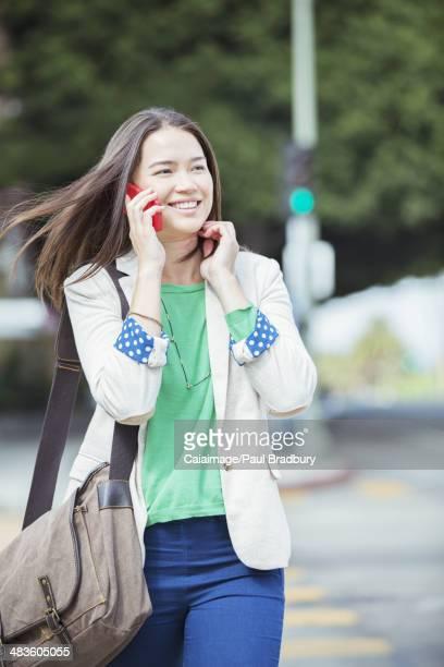 Happy businesswoman talking on cell phone in crosswalk